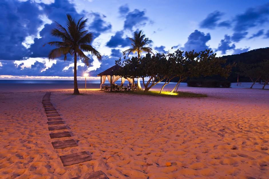 马拉西亚婆罗洲的在沙巴,享有风下之乡和神山圣土的美誉。是知名的旅游天堂。在这里,可以看到世界上最美的落日。沙巴海岸线朝西,而西边的海平面上又排列几处岛屿,每年大部分时间的傍晚都可见红霞落日。   海边绚烂的夕阳,我见过不少,冬日的冰海在红日下是那样的悲怆,令人神伤;鼓浪屿的海与回忆相牵,微笑中带着泪水。而此时,我真实的站在沙巴的海岸上,看着海浪拍打岸边激起沸腾的浪花,沐浴着蜜色夕阳的海边小屋倏地灵动起来,夕阳渐渐地收敛了光芒,变得温和起来,像一只光