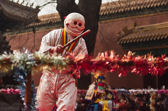 23/38 舞者头戴骷髅面具,身着白色短衣和白色缎裤,腰间系红色绸带,裤