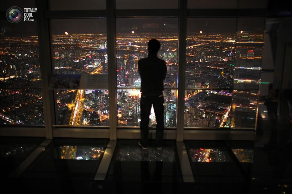 一位男子站在上海市中心的落地窗前看夜景- 深瞳渊源,品味经典!