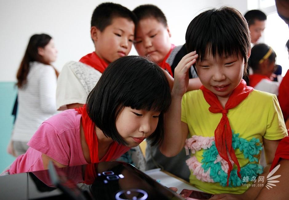 志愿者教孩子们怎么使用打印机打出自己拍摄的照片.