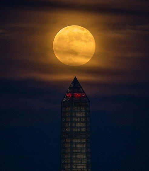 013年6月23日,一轮超级月亮从华盛顿纪念碑后冉冉升起.