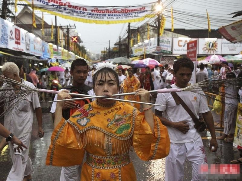 当地时间2012年10月20日,泰国普吉岛,民众参加素食节庆祝活动。   据泰国国家旅游局官网资料显示,泰国素食节(Phuket Vegetarian Festival)据称来源于中国,在中国的阴历九月举行,人们相信素食节以及与之相伴的宗教仪式都将给那些参加仪式的教徒们带来好运。节日期间,民众戒吃肉、戒喝酒、戒色欲、戒争吵、戒诳语、戒杀生。普吉素食节长达九天,最震撼眼球的是其中的穿刺表演,他们通过这种痛苦的行为来洗刷他们的罪孽,除此之外,还有灵媒活动、需